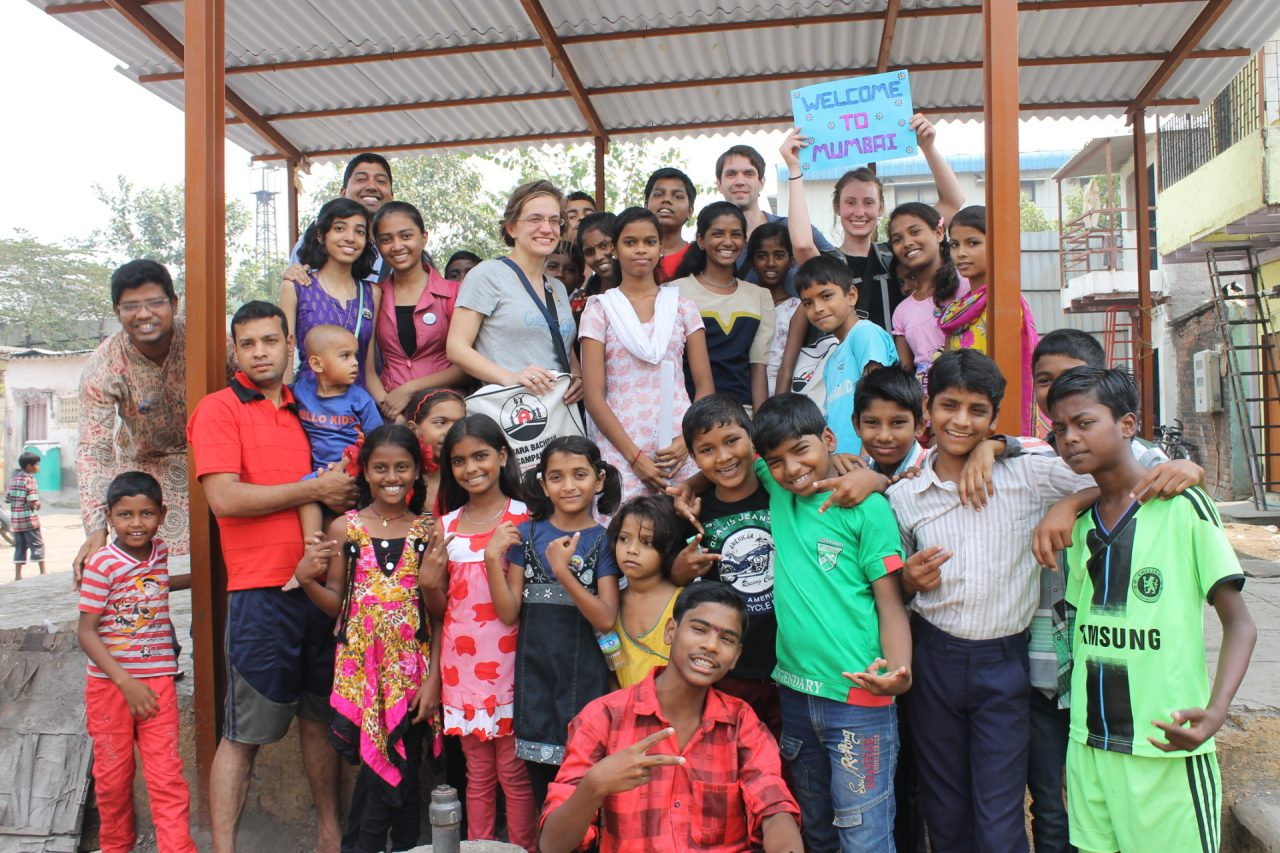 Students with large group of children in Mumbai, India