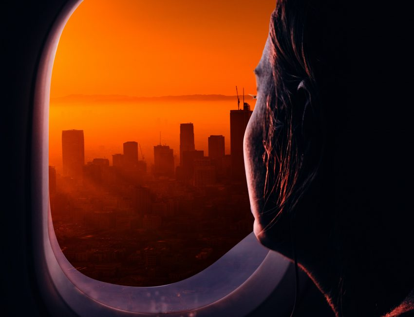 Woman looking out of an airplane window at a cityscape