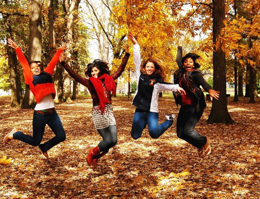 four students jumping in the fall leaves