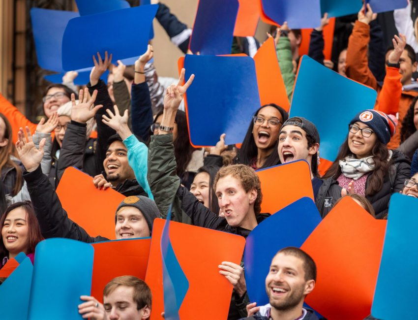 smiling students at event holding orange and blue signs