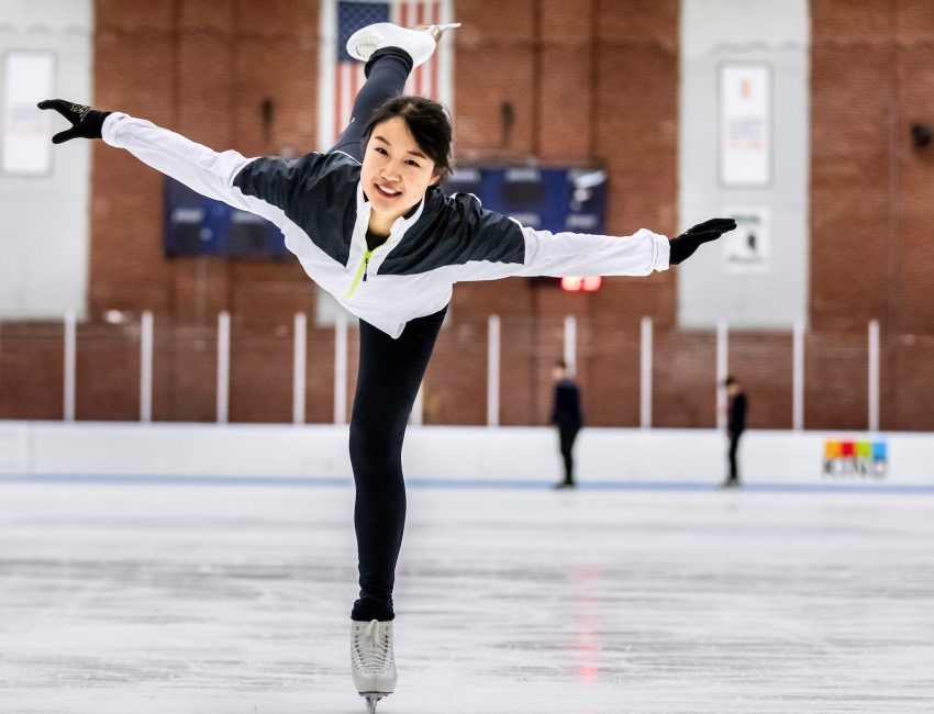student ice skating on one foot with arms outstretched