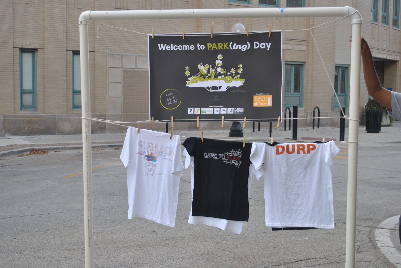 PARK(ing) Day sign in downtown Champaign, hanging over DURP t-shirts