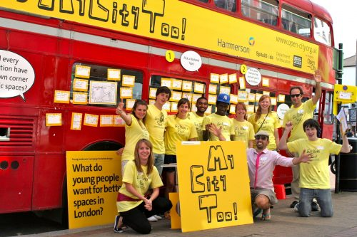 Young people in front of a red double-decker bus