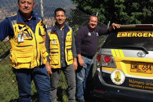 Dr. Sarmiento and two other men by an emergency vehicle, dressed in yellow safety vests