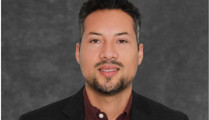 Photo of Dr. Sarmiento with dark gray background