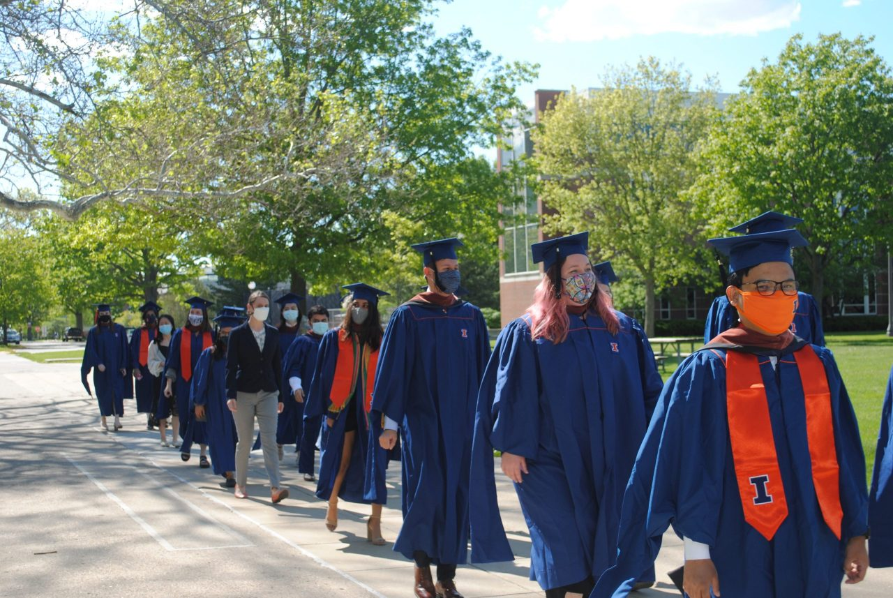 Students in cap and gown parading on quad