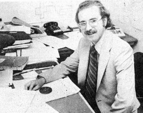 Black and white photo of Doug Houston sitting at office desk surrounded by papers and maps on the wall.