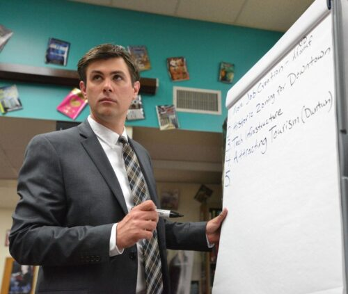 Photo of Drew Awsumb in front of a white board during a presentation.