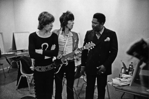 Black and white photo of Mick Jagger, Keith Richards and B.B. King . Keith Richards is holding a guitar as he talks to B.B. King.
