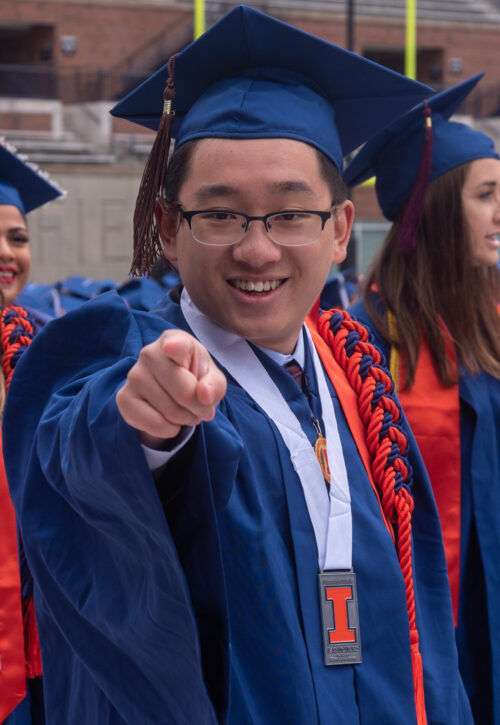 Photo of Zishen Ye in blue cap and gown with orange cords pointing to camera