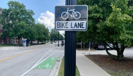 Photo of bike lane sign and actually bike lane along side of a rode on UIUC campus