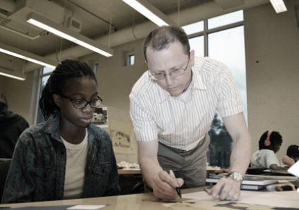 Professor and students looking over work in studio