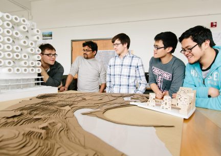 Students in design studio with a model