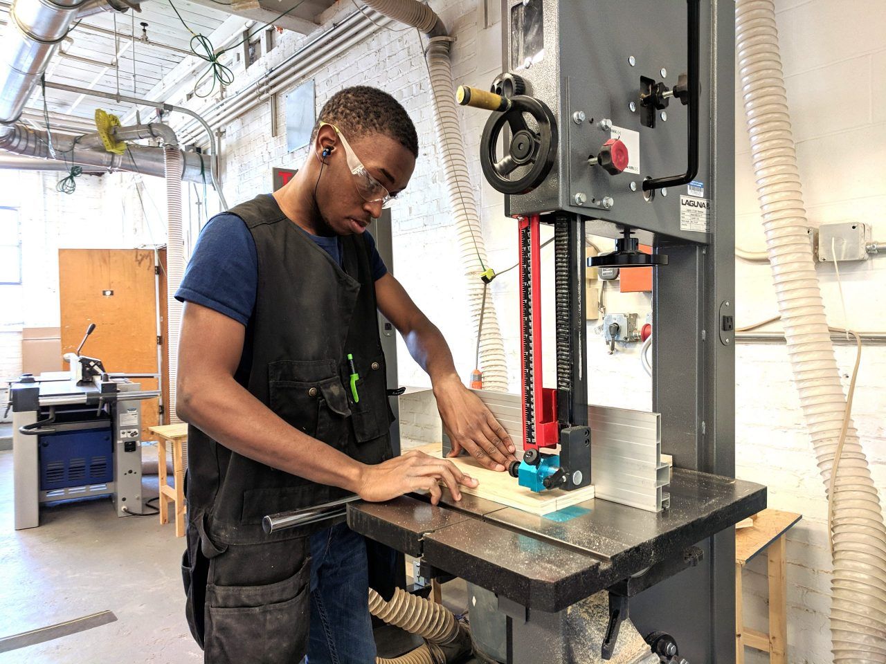 Student using a bandsaw in the woodshop