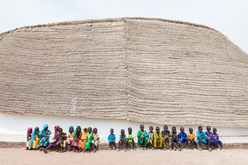 exterior image of school in senegal with students in front of building