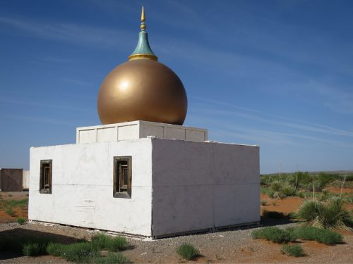 golden onion dome on a small white building