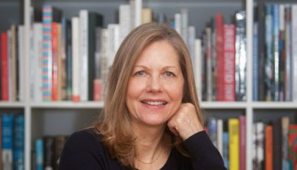 headshot of Martha Thorne with bookcase behind her
