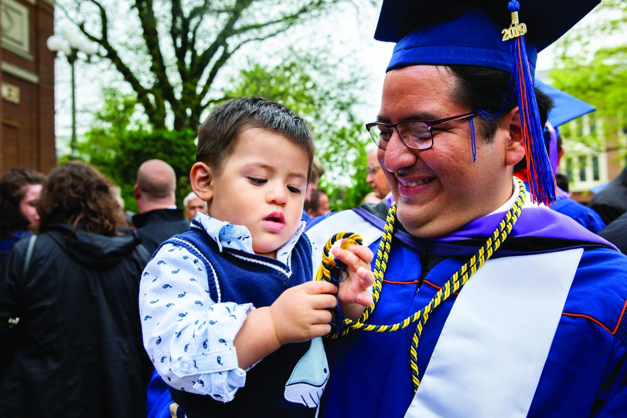 Adult in graduation garb holding young boy