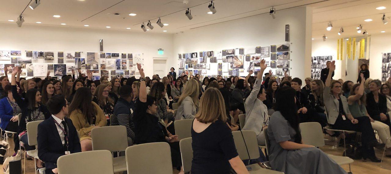 audience members raising hands at the symposium
