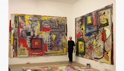 Tom Goldenberg with two paintings in his studio