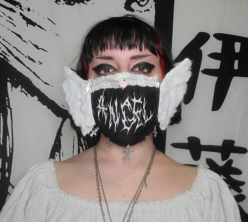 Woman wearing a black mask with a white pattern and white wings