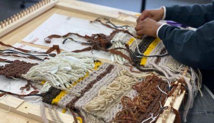 Weaving with loom and student's hands