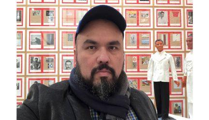 Jorge Lucero in front of art exhibit