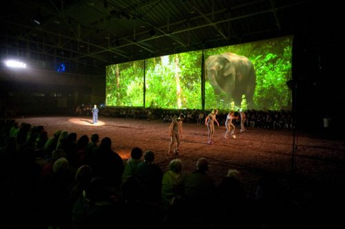 Performance view of the Unreliable Bestiary showing projection, performers, and audience