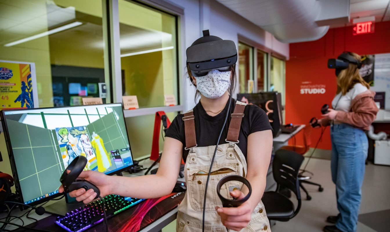 Photo of two students using VR headsets and hand held controllers in a computer lab