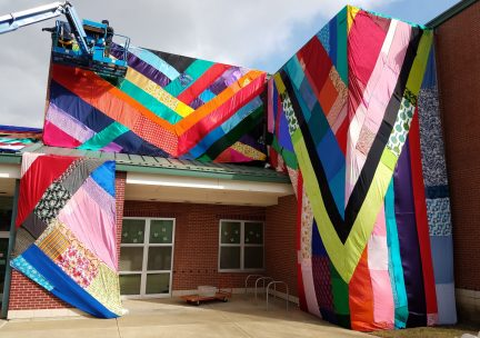 Photo of color fabric installation by surrounding the entrance of an elementary school.