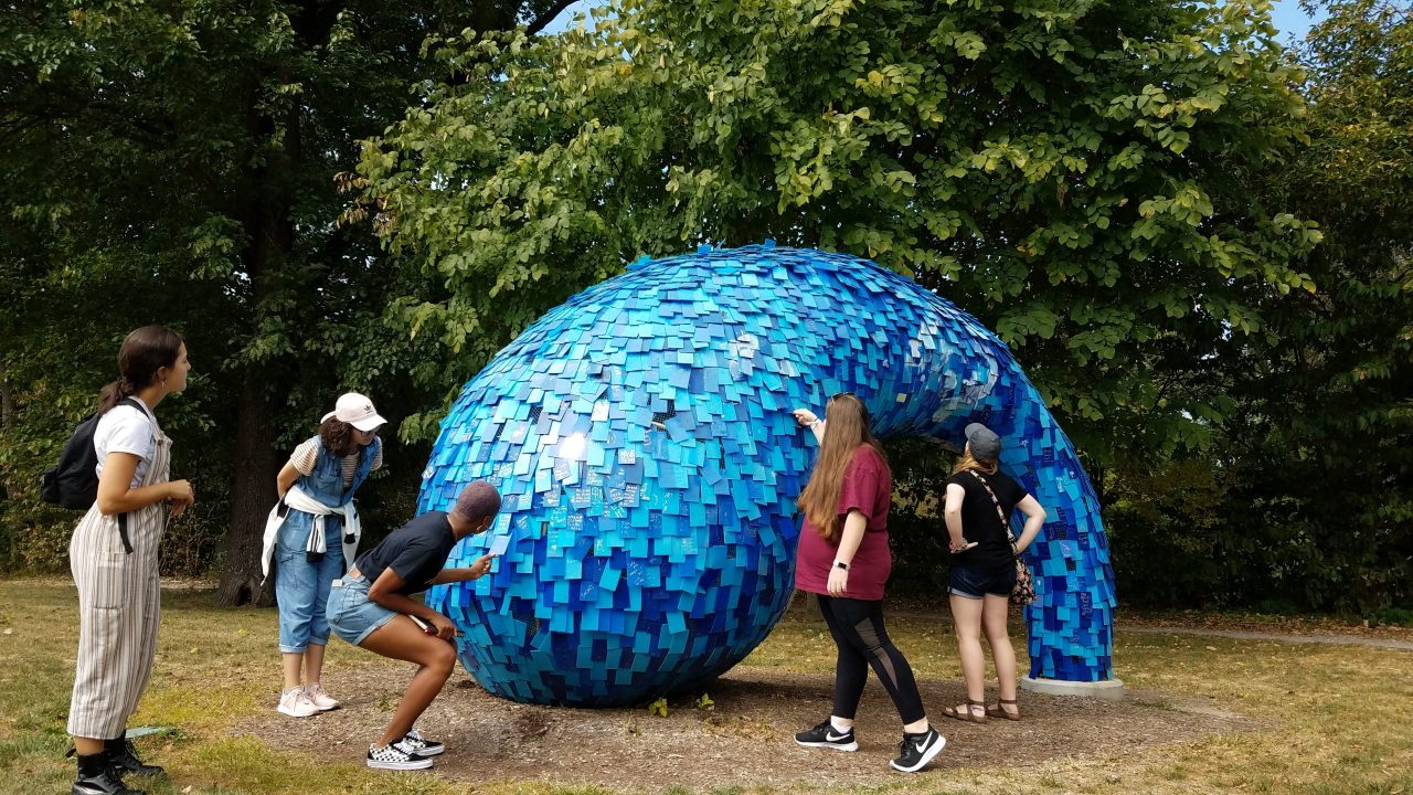 Students gathered around a large blue outdoor sculpture.