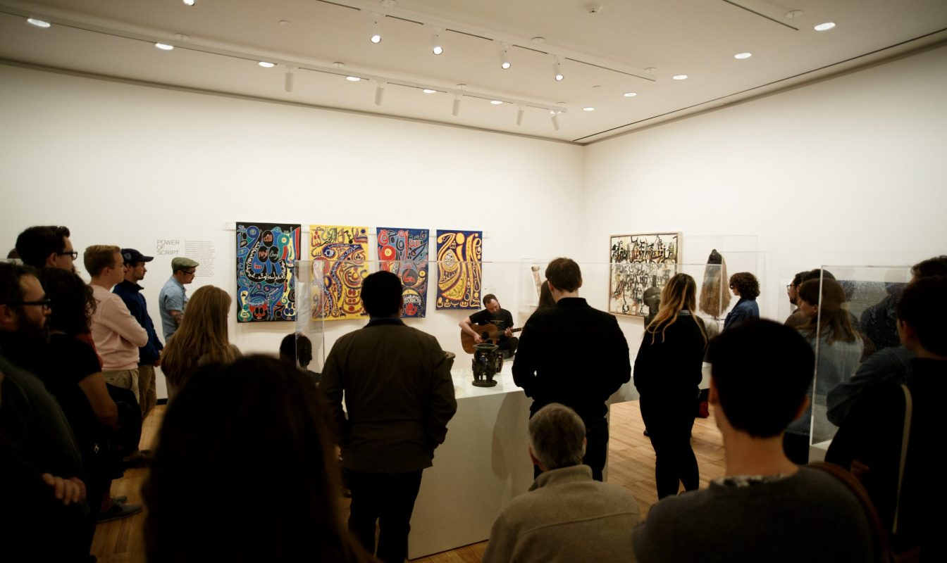 Photo of students and faculty engaged in critique in a gallery