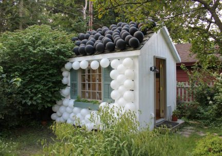 Photo of a small white house with black and white balls on the wall and roof