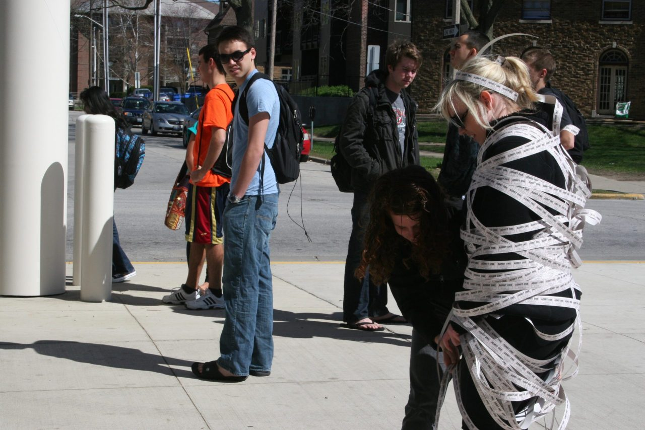 Photo of students on a street looking at a student wrapped in strips of paper printed with text
