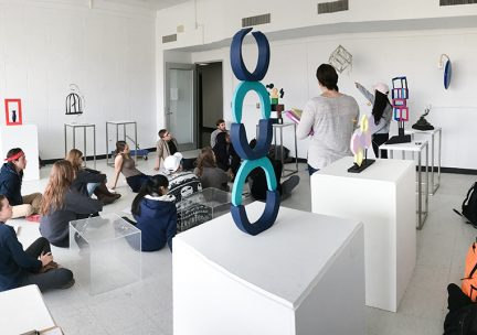 Photo of students sitting cross legged in an art gallery discussing the work