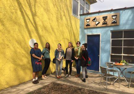 Photo of a group of doctoral students outdoors before a yellow wall