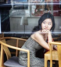 Portrait of the seated student through a plate glass window