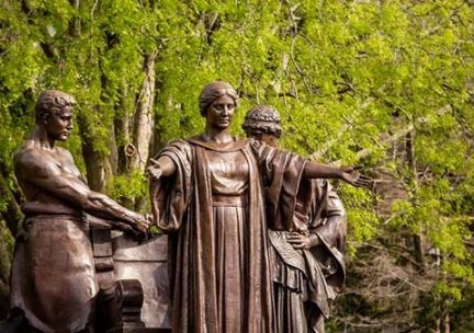 Photo of the Alma Mater statue group with green trees in the background