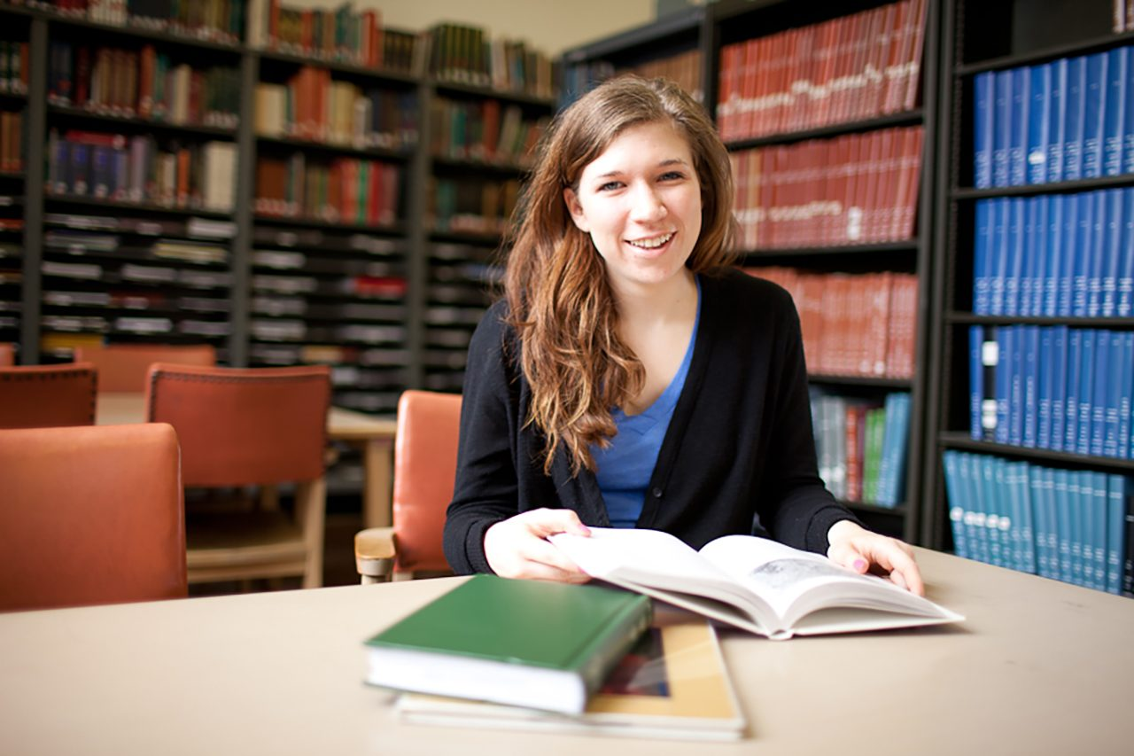 Smiling student with books at a library table