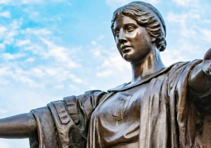 Closeup photo of Alma Mater statue with upraised arms