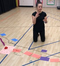 Portrait of the student working with colored paper on a school gymnasium-style floor