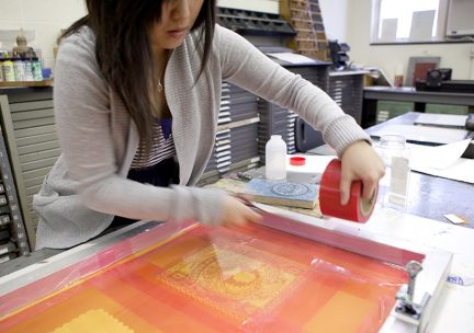 Photo of a student printing from a red and orange silkscreen