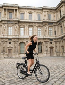 Photo of the student riding a bicycle on cobblestones in a historic European courtyard