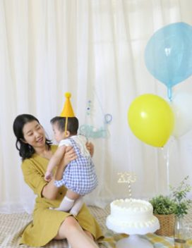 Photo of a figure in a yellow dress holding a small child with a birthday cake and balloons