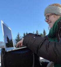 Portrait of the smiling student working on a laptop outdoors in a winter landscape