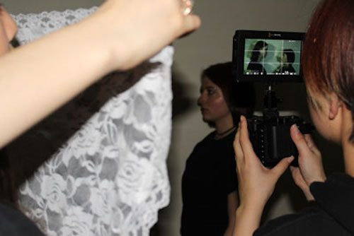 Photo of a student recording two students with a video camera