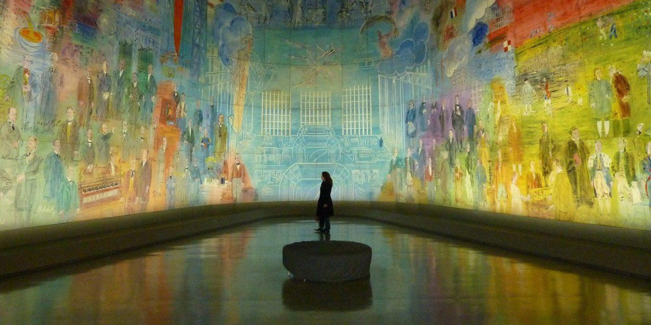 Photo of museum visitor standing in a large curved mural installation