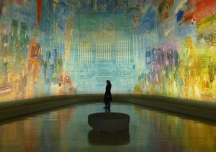 Photo of figure standing in a large curved mural