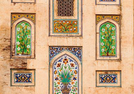 Photo of colorful mosaics set into an architectural façade.