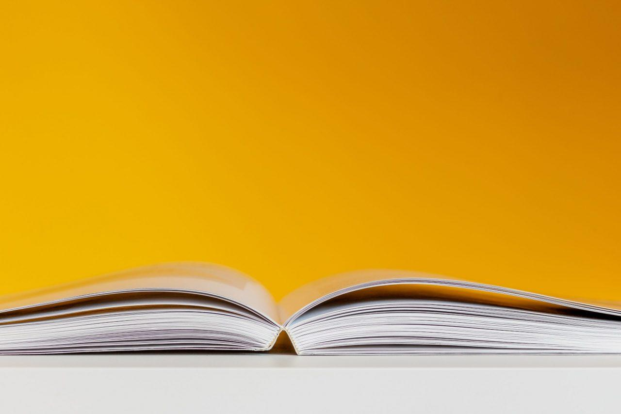 Eye-level view of an open book against a yellow background